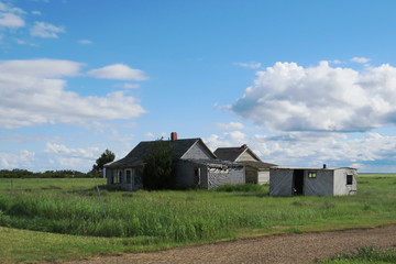 Many old houses and a storage unit in the middle of a field in Saskatchewan, Canada.