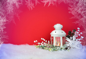 Christmas Eve lantern and decorations background. Picture of a white lantern with lighted candle decorated with pine cones  on a white snow against red frost background