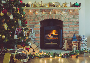 Toned photo of beautiful Christmas setting, decorated fireplace with woodburner, lit up Christmas tree with baubles and ornaments, lantern, stars, candles, selective focus