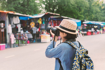 young asian woman traveler taking photo on street market