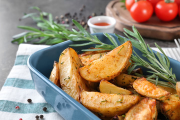 Delicious baked potatoes with rosemary in baking dish on cloth