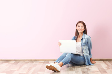 Young lady with modern laptop sitting on floor near color wall