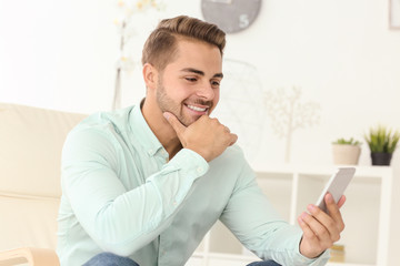 Young handsome man using his mobile phone while sitting in armchair at home