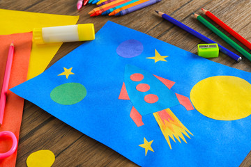 Child's applique of rocket on wooden table