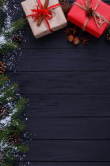 Christmas, New year holidays composition. Gift boxes and fir tree branches with snowflakes on black wooden background with copy space for your text design