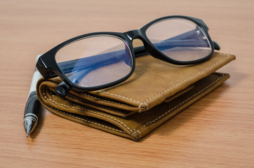 Eyeglasses, pencil, and wallet