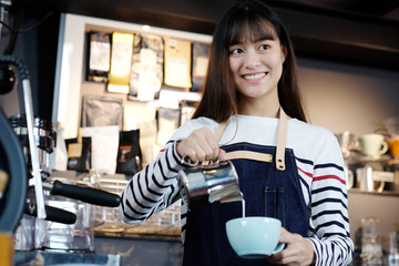 Young asian women barista pouring milk into coffee cup at cafe counter, food and drink concept