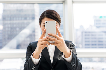 young businesswoman taking a picture with smart phone