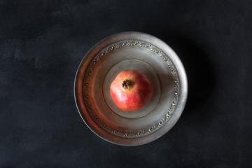Ripe pomegranate on a metallic plate on a dark background