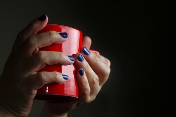 Hands with polished nails holding a red mug