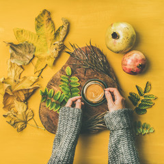 Autumn morning coffee concept. Flat-lay of woman' s hands in grey woolen sweater holding cup of espresso over mustard yellow background with dried leaves and pomegranates around, top view, square crop