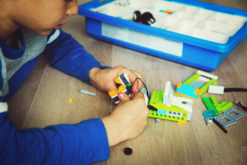 teenage boy building from colorful plastic blocks