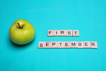 First september. Conception with apple and inscription on blue background.