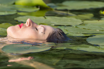 Beautiful young woman with blue eyes in the water
