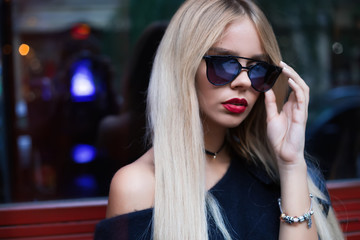 High fashion look.glamor closeup portrait of beautiful sexy stylish Caucasian young woman model with bright makeup, with red lips, with perfect clean skin.in sunglasses walking in the street.