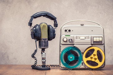 Retro reel to reel tape recorder circa 60s, microphone and headphones on wooden table front concrete wall background. Vintage style filtered photo