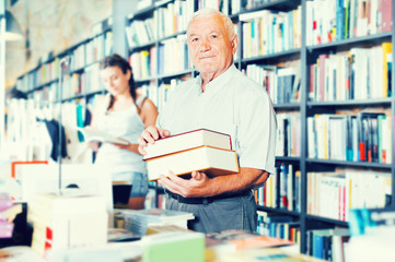 Mature man is showing book that he bought