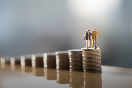 Concept of retirement planning. Miniature people: Old couple figure standing on top of coin stack.