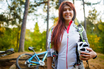 Photo of young sporty brunette with helmet on background of bicycle
