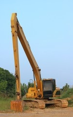 Big yellow excavator with long boom moving to the parking.