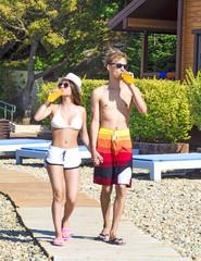 Jolly youthful couple enjoying summer drinks on resort