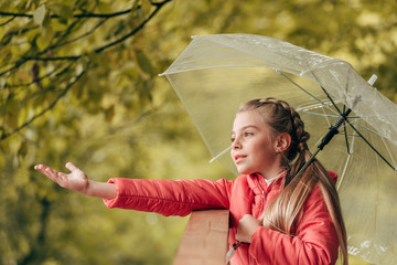 child with umbrella in autumn park