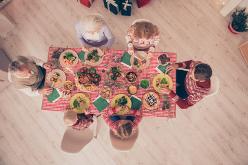 High angle view of six gathered relatives, setted festive desktop, yummy treats, parents, siblings, in traditional x mas costumes, gifts boxes. Bon appetite! Christmastime!