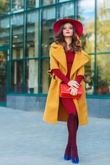 Young beautiful women in a yellow coat, outdoor