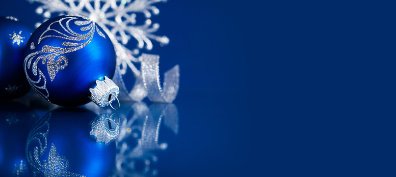 Blue christmas ornaments on blue background. Merry christmas greeting card, banner. Winter holiday xmas theme. Happy New Year.