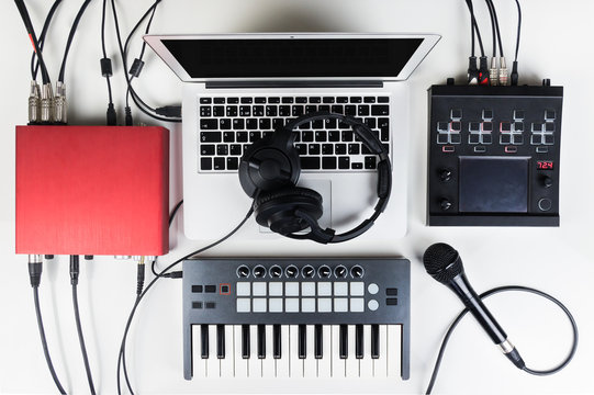 Portable and compact music home studio for electronic and beat music production. Top view of modern music recording set up with professional headphones, software controllers, digital effect processors