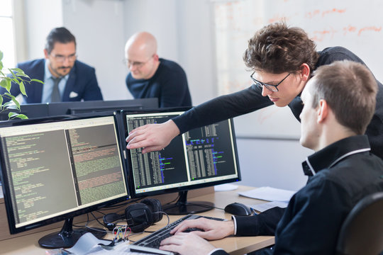Startup business and entrepreneurship problem solving. Young AI programmers and IT software developers team brainstorming and programming on desktop computer in startup company share office space.