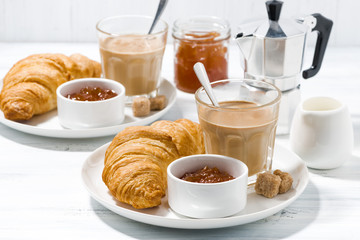 coffee with milk and croissants with jam for breakfast on white table