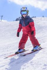 kleiner Junge bei einer Schußfahrt auf der Skipiste