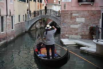 Well-uniformed condolier on a gondola, Venice