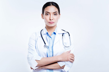 Pretty female doctor posing with her arms folded