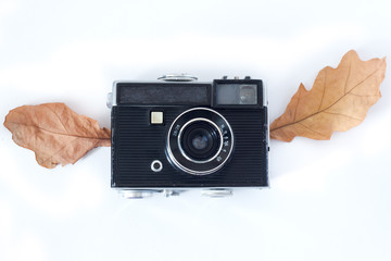 Vintage Analogue Photo Camera with wings Dry Maple Leaves on white background, Top View .