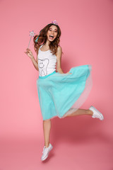 Full length photo of charming brunette woman dressed like tooth fairy holding magic wand jumping and looking at camera while jumping