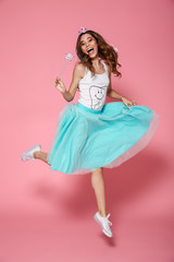 Full length photo of cheerful princess, looking at camera, holding magic wand while jumping over pink background
