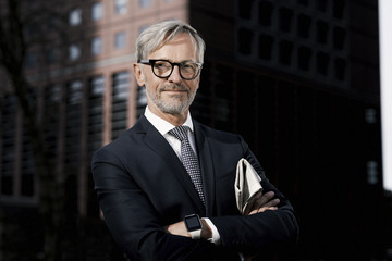 Portrait of confident grey-haired businessman outdoors