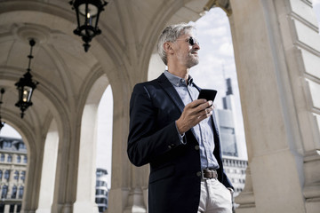 Grey-haired businessman in the city holding smartphone