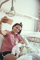 Mother taking a selfie with her newborn baby in hospital bed