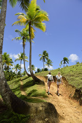 Dominican Republic, Samana, two women hiking on path with palm trees