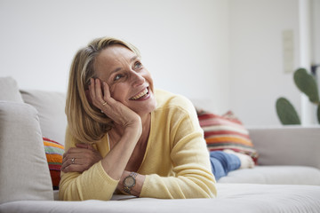 Smiling mature woman at home daydreaming on the sofa