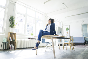 Businesswoman sitting on table in a loft