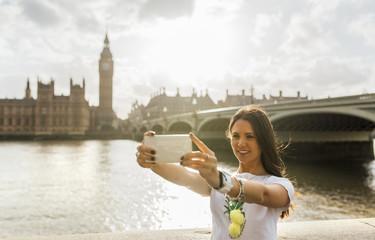 UK, London, beautiful woman taking a selfie near Westminster Bridge