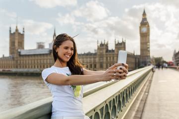 Beautiful woman taking a selfie on Westminster Bridge, London, United Kingdom