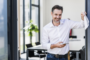 Portrait of smiling businessman holding cell phone