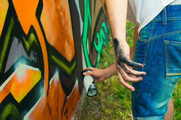 The artist draws graffiti. The artist's hand in paint.