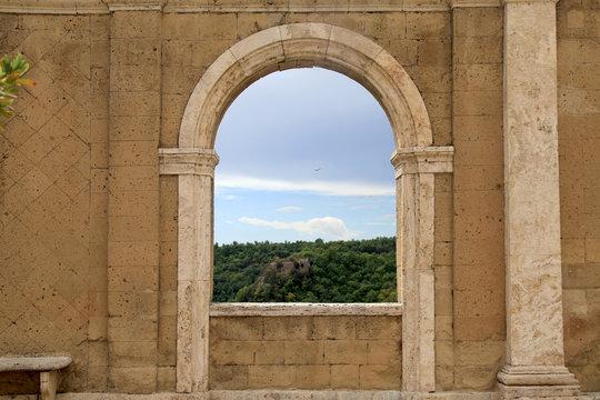 Italian view through the arch window in Sorano, Tuscany, Italy.