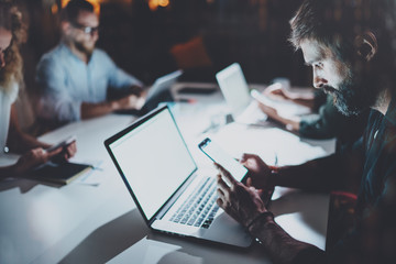 Bearded young man working at night office with partners.People using contemporary laptop and modern smartphones.Horizontal.Blurred background.